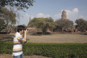 Asian man photographing outside temple
