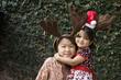 Girls wearing reindeer antlers and hugging