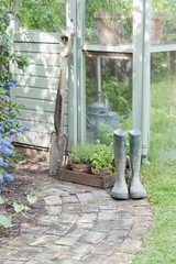 Garden tools and wellington boots outside greenhouse