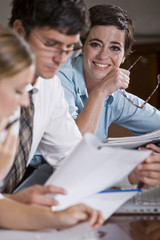 Female office worker with colleagues reading reports