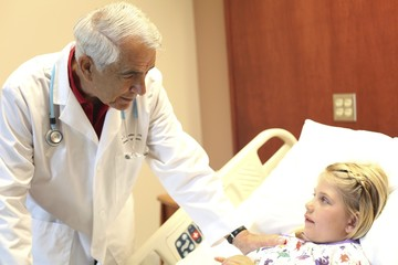Elderly doctor leans over patient in pediatrics ward