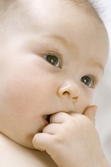 Infant child chewing on hand