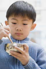 Chinese boy eating with chopsticks