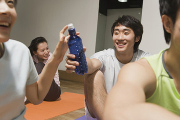 Chinese man handing woman water bottle in exercise class