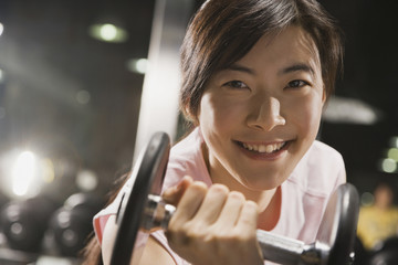 Chinese woman holding dumbbell