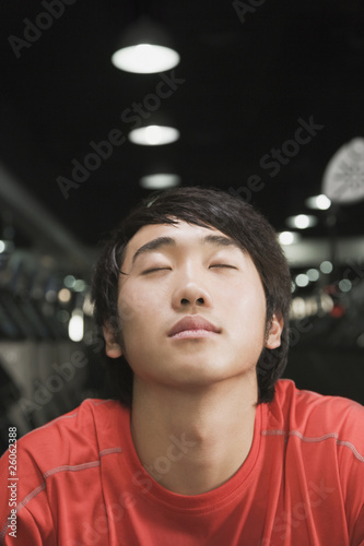 Chinese man with eyes closed in health club