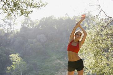 Hispanic woman stretching arms overhead