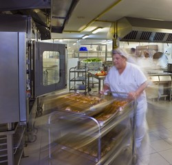 Kitchen porter pushes a trolley of pastries