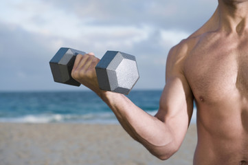 Mixed race man doing biceps curls on beach