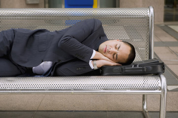 Mixed race businessman sleeping on bench