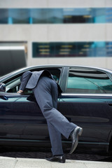 Mixed race businessman leaning in car window