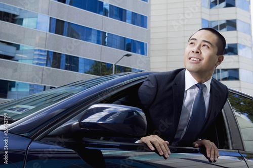 Mixed race businessman leaning out car window