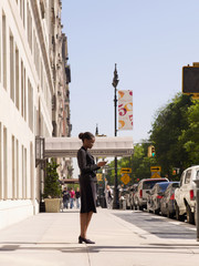 African businesswoman looking at cell phone on sidewalk