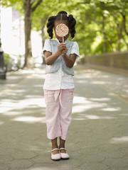 African girl hiding behind lollipop