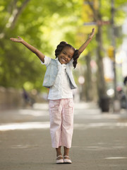 African girl smiling with arms raised