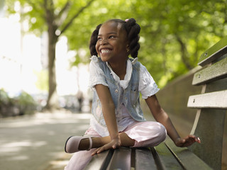 African girl smiling on bench