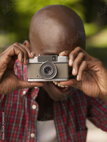 African man taking photograph with retro camera