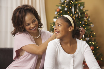 Mother fixing daughterÕs hair in front of Christmas tree