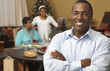 Man smiling with family at dinner table in background