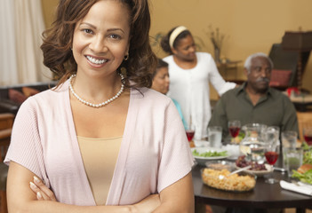 Woman smiling with family at dinner table in background
