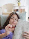Hispanic woman doing newspaper crossword puzzle