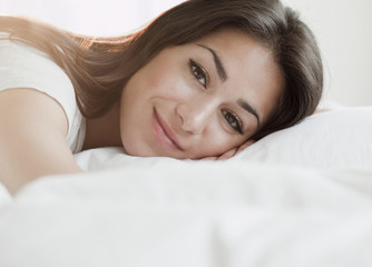 Hispanic woman laying on bed