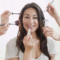 Hands applying makeup to Hispanic womanÕs face