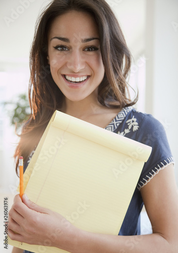 Hispanic woman holding notepad and pencil