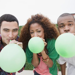 Friends blowing up green balloons