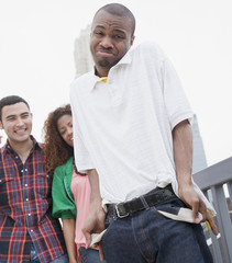 African man showing empty pockets with friends in background