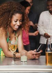 Woman text messaging at bar