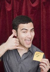 Mixed race man holding Call Me sticky note and gesturing