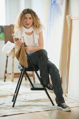 Hispanic woman holding paintbrush