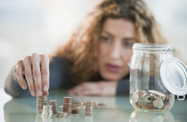Hispanic woman counting coins from jar