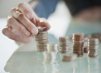 Close up of Hispanic woman stacking coins