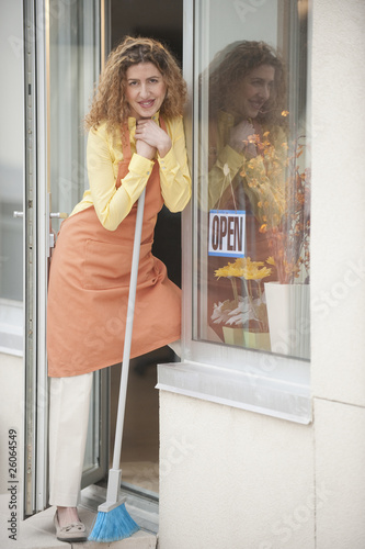 Hispanic shopkeeper holding broom in doorway