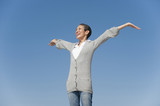 Chinese woman smiling with arms outstretched against blue sky