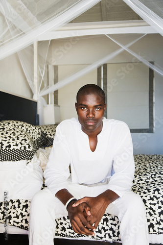 Serious African man sitting on edge of bed