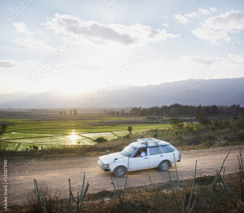 Car driving along dirt road in countryside