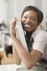 African businesswoman hugging computer