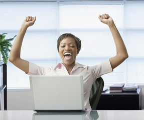 African woman with laptop celebrating
