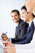 Three successful businesspeople at meeting, presentation