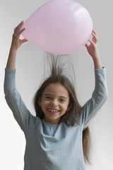 Hispanic girl creating static in hair with balloon
