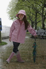 Hispanic girl wearing rain gear in rainy park