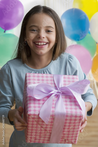 Hispanic girl holding birthday gift and smiling