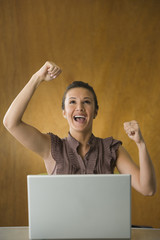 Woman with laptop celebrating