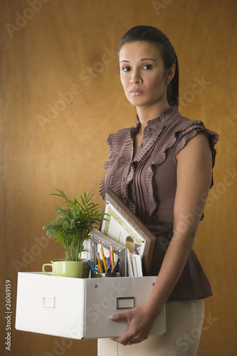 Businesswoman holding office belongings