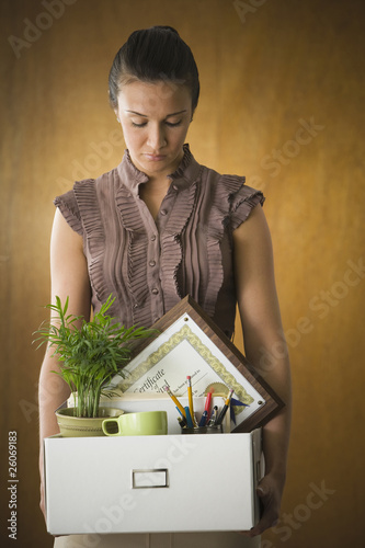 Dejected businesswoman holding box of office belongings