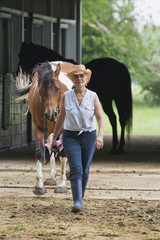 Hispanic woman walking horse