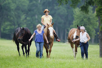 Multi-generation Hispanic women walking and riding horses in field